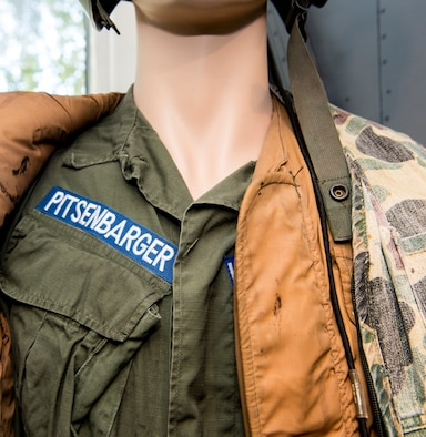 A uniform belonging to the late U.S. Air Force Airman 1st Class William Pitsenbarger, medal of honor recipient pararescue crew member, has a uniform displayed in the Pitsenbarger Heritage Hall at Spangdahlem Air Base, Germany, August 5, 2020. Airman Pitsenbarger is highlighted throughout the hall in addition to having his own corner dedicated to his bravery and sacrifice. The Pitsenbarger Heritage Hall is named in his honor for waiving off a helicopter while he continued to fight enemies during the Vietnam War, saving 60 other men and sacrificing his life. (U.S. Air Force photo by Airman 1st Class Alex Miller)