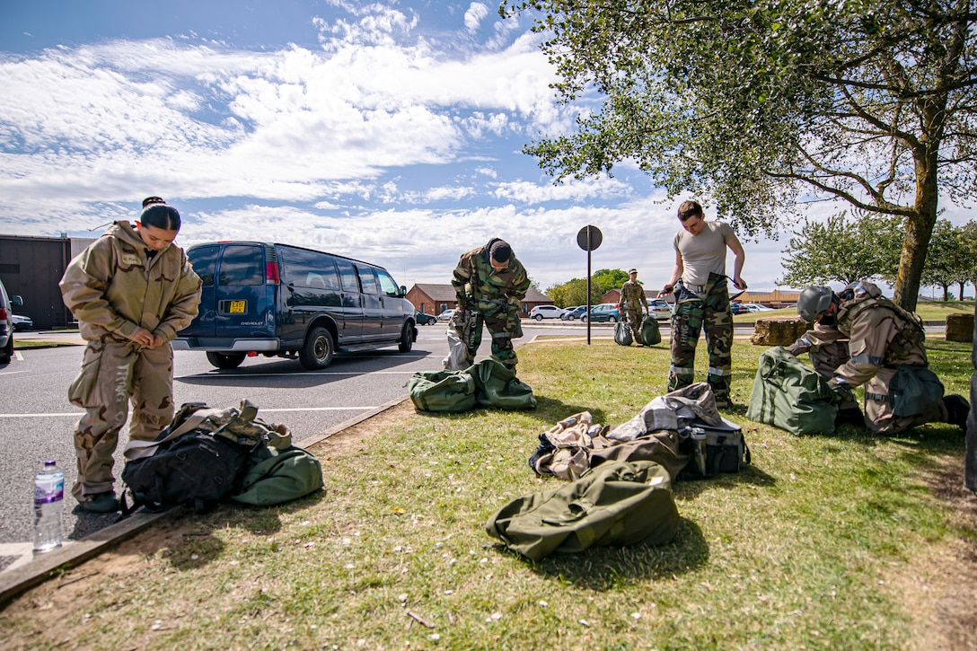 U.S. Air Force Airmen from the 501st Combat Support Wing, put on their mission oriented protective posture gear during a wing readiness exercise at RAF Alconbury, England, Aug. 5, 2020. The 501st CSW conducted the exercise to evaluate Airmen's overall readiness along with their proficiency with responding to simulated chemical, biological, radiological, nuclear and explosive attacks. (U.S. Air Force photo illustration by Senior Airman Eugene Oliver)