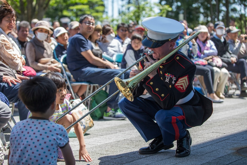 A Marine plays a trombone for an audience.