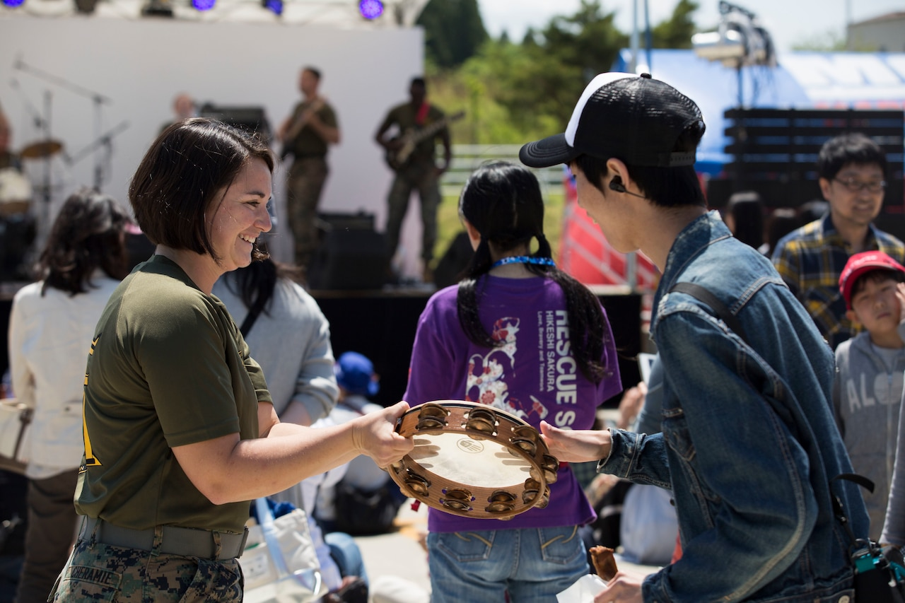 Two people play a tambourine.