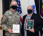 """Maj. Gen. Dennis P. LeMaster, commanding general of the U.S Army Medical Center of Excellence at Joint Base San Antonio-Fort Sam Houston, presents Robert """"Bob"""" Preshong, Department of Combat Medic Training, with the U.S. Army Training and Doctrine Command, or TRADOC, Civilian Instructor of the Year award and a letter from Gen. Paul E. Funk II, TRADOC commanding general."""