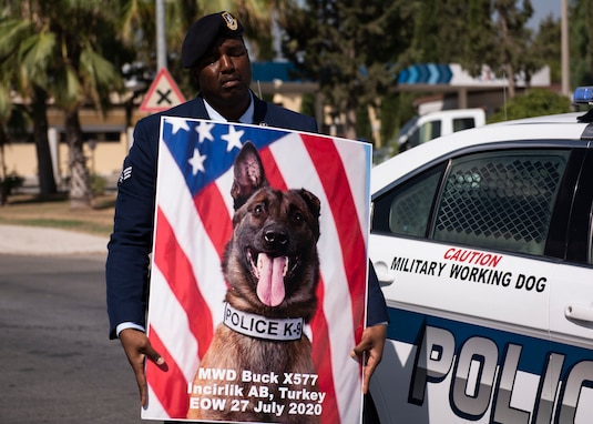 U.S. Senior Airman Antoine Carr, 39th Security Forces Squadron military working dog handler, holds the memorial poster of MWD Buck Aug. 5, 2020, at Incirlik Air Base, Turkey.