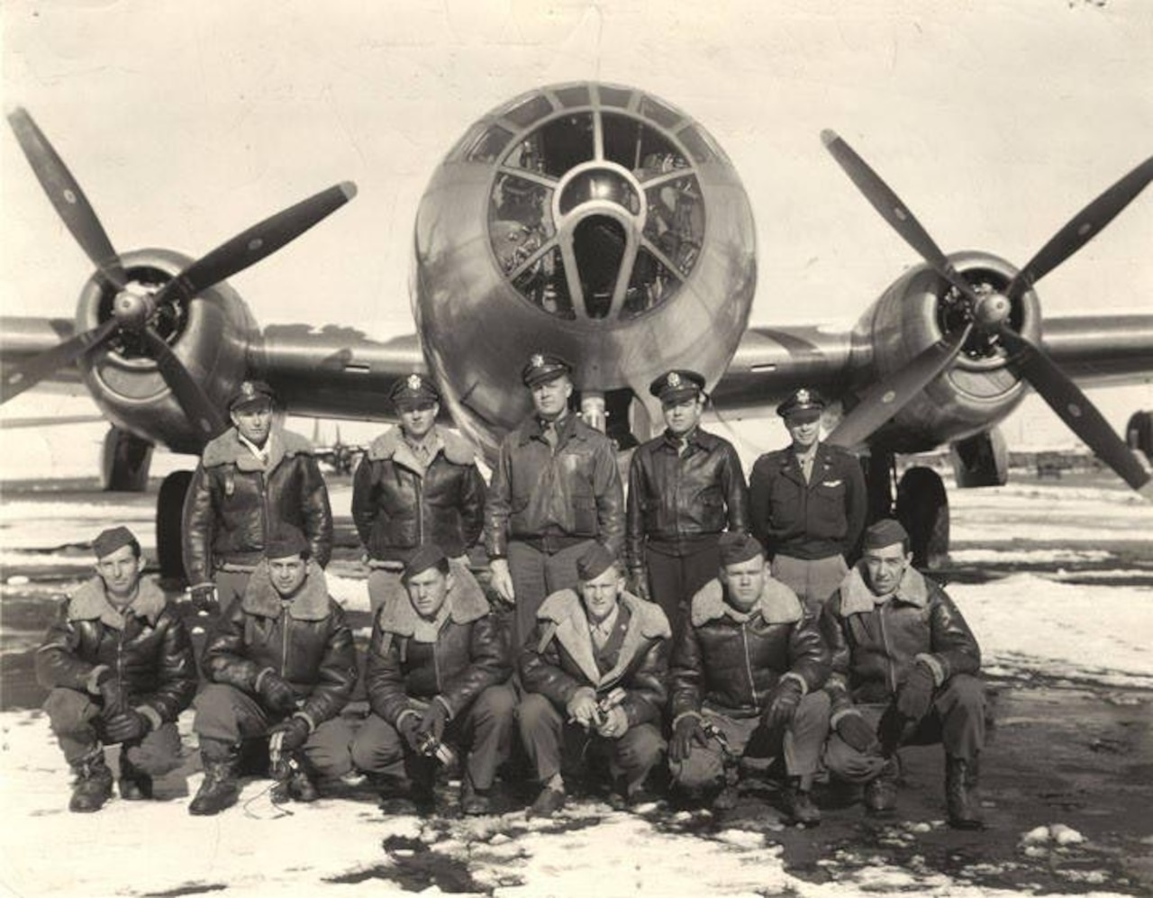 Eleven men pose in front of a B-29 bomber.