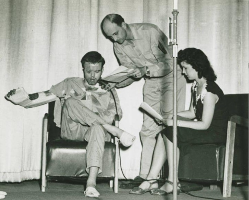 An injured man talks into a microphone another man is holding. A woman sits beside them.