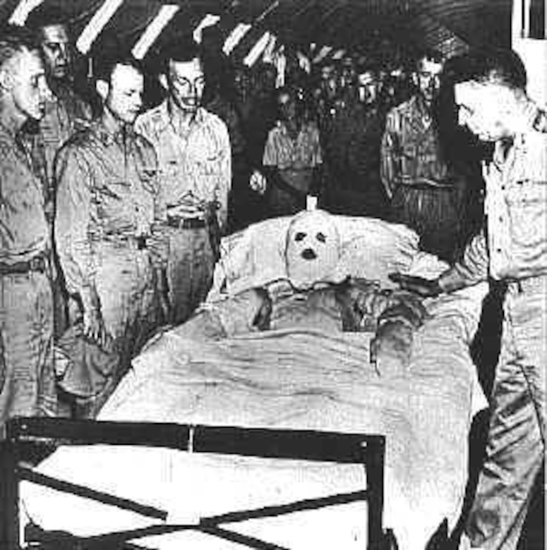 A man covered in bandages in a hospital bed is surrounded by soldiers.