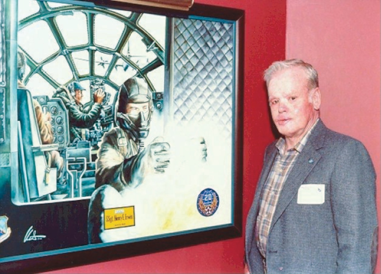 A man stands to the right of a painting depicting action inside an airplane.