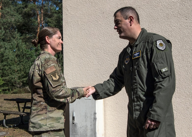 U.S. Air Force Tech. Sgt. Amber Coronado, 86th Airlift Wing Judge Advocate noncommissioned officer in charge of adverse actions, left, receives a coin from Brig. Gen. Mark R. August, 86th Airlift Wing commander, after being named Airlifter of the Week at Ramstein Air Base, Germany, July 31, 2020.