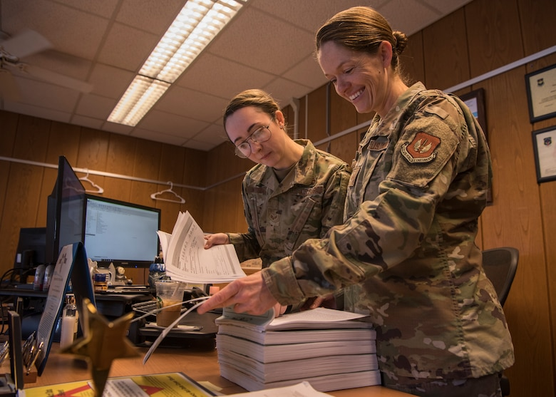 U.S. Air Force Tech. Sgt. Amber Coronado, 86th Airlift Wing Judge Advocate noncommissioned officer in charge of adverse actions, right, and Senior Airman Katrina Walter, 86th AW JA military justice paralegal, look through documents at Ramstein Air Base, Germany, Aug 4, 2020.