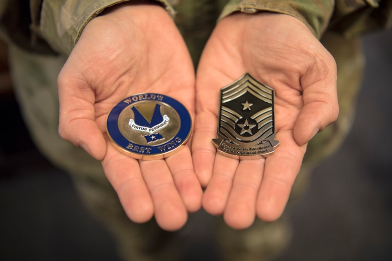 U.S. Air Force Tech. Sgt. Amber Coronado, 86th Airlift Wing Judge Advocate noncommissioned officer in charge of adverse actions, holds coins presented by the base commander and command chief for being Airlifter of the Week at Ramstein Air Base, Germany, Aug. 4, 2020.