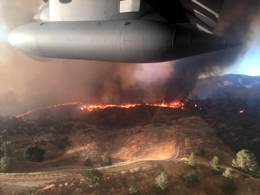 Large military aircraft flies over fires in California.