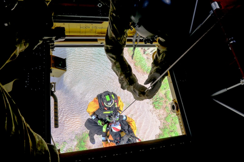 Pennsylvania National Guard members joined with partners in the Helicopter Aquatic Rescue Team (PA-HART) and other civilian first responders in a full-scale exercise at Fort Hunter Park and the Susquehanna River Aug. 15. A Guard member lowers a HART technician through the center hoist to retrieve a simulated casualty. (U.S. Army National Guard photo by Staff Sgt. Zane Craig)