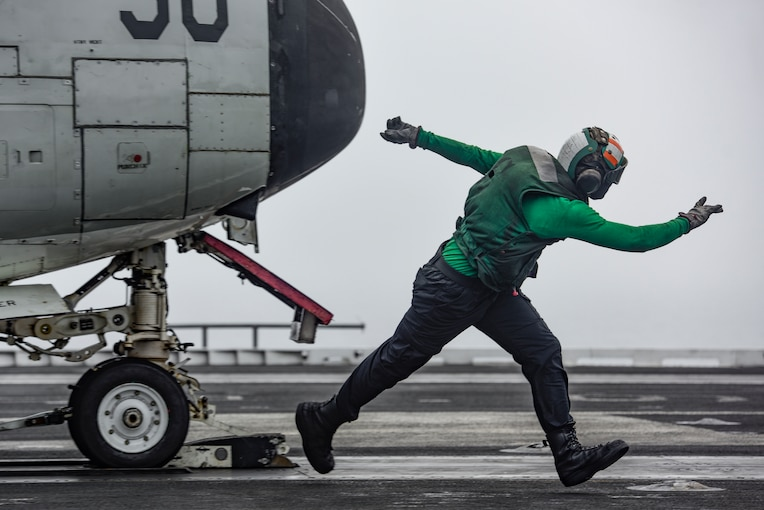 An airman signals an aircraft on a flight deck.