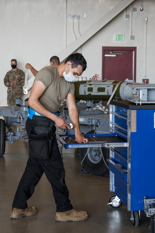 U.S. Air Force Airmen 1st Class Christian Cortez, 525th Aircraft Maintenance Unit weapons load crew member, grabs tools in preparation for the 2nd Quarterly Wing Load Crew competition, at Joint Base Elmendorf-Richardson, Alaska, July 31, 2020. The event consisted of the 90th AMU and 525th AMU testing their technical expertise with a basic knowledge test, composite tool kit inspection, uniform inspection, and F-22 weapons load out.