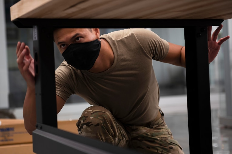 An airman wearing a face mask assembles a desk.