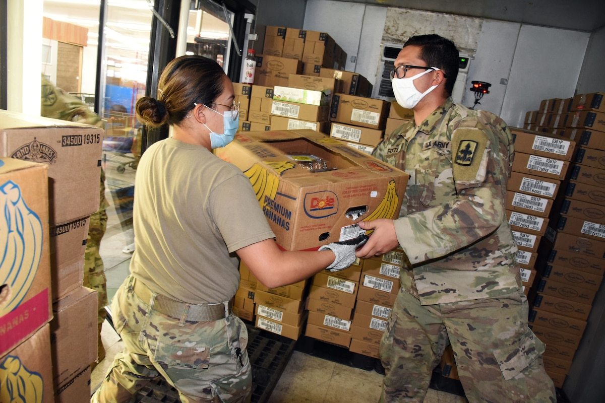 Two soldiers, one wearing a face mask and gloves and one wearing a face mask, carry a box of food that will be distributed at a local food bank.
