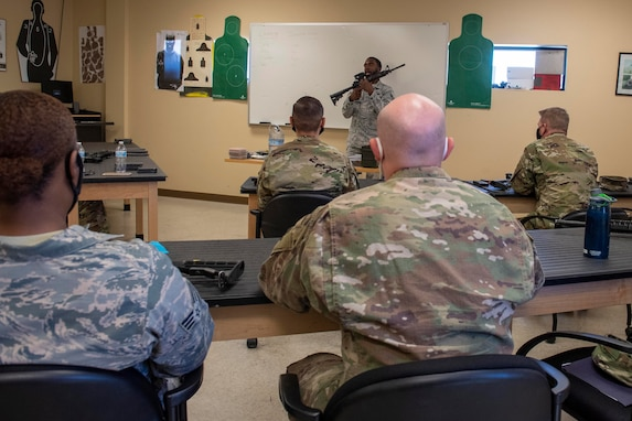 A male instructor holds up an M4 carbine in front of a class of Airmen