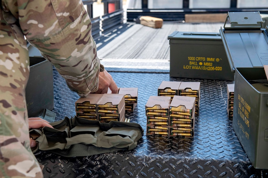 A male Airman unboxes ammunition