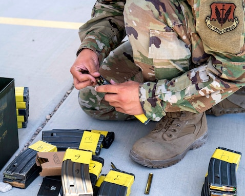 A male Airman student loads ammunition into an M4 carbine magazine