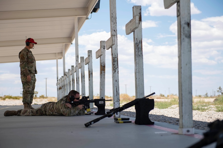 A CATM instructor observes as a male student fires an M4 carbine