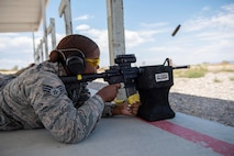 A female Airman lays in the prone position while firing an M4 carbine.