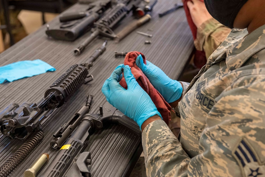A female Airman disassembles and cleans an M4 carbine.