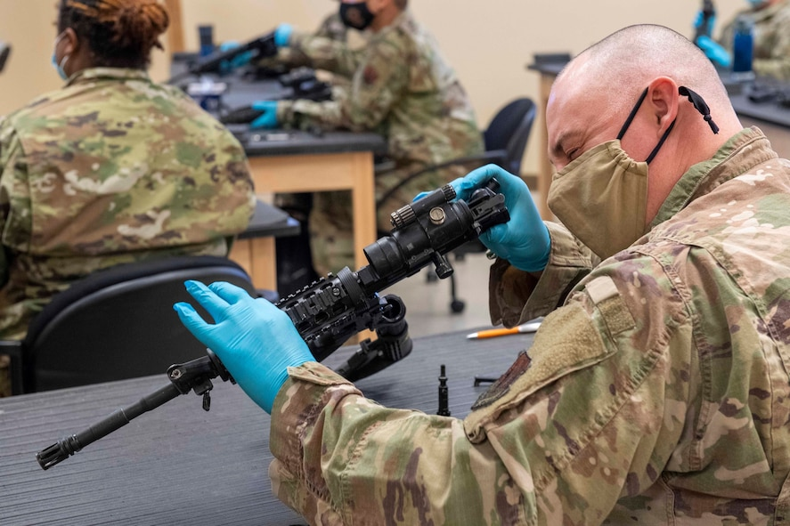 Airman examines the barrel of an M4 carbine
