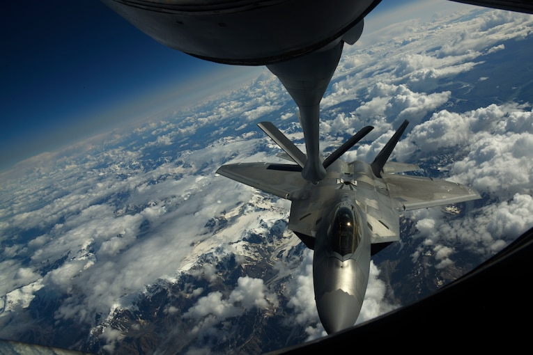 An aircraft prepares to refuel above the clouds.