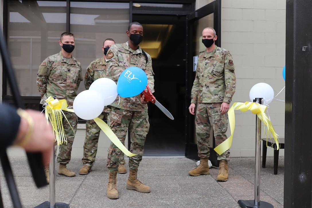 A 381st Training Group student cuts the ribbon to officially reopen The Beachcombers dining facility at Vandenberg AFB, California, Aug. 6, 2020.
