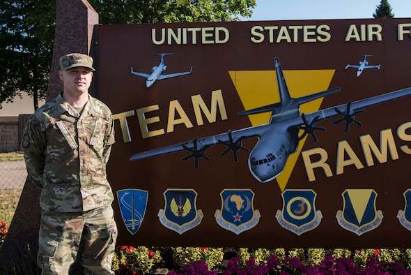 U.S. Air Force Staff Sgt. Corey Drake, 1st Combat Communications client systems technician, stands in front of a wing sign at Ramstein Air Base.
