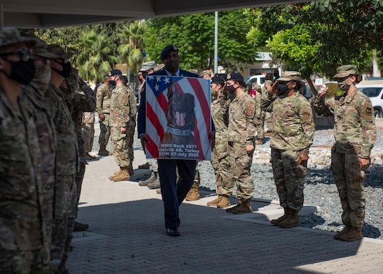 U.S. Senior Airman Antoine Carr holds a memorial poster of MWD Buck while walking past saluting SFS Airmen, Aug. 5, 2020, at Incirlik Air Base, Turkey.