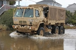 Members of the North Carolina National Guard drive vehicles assigned to the 878th Engineer Vertical Construction Company, 105th Engineer Battalion, through flooded roads to assist stranded people on Oak Island, North Carolina, Aug. 5, 2020. The NCNG deployed teams across the eastern portion of the state to help respond after Hurricane Isaias.