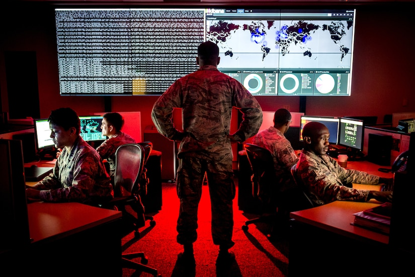 Military personnel sit at computer terminals in a room with a large screen.  One service member is standing.