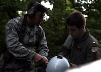 U.S. Air Force Tech. Sgt. Kevin Zamora, 35th Operation Support Squadron Survival, Evasion, Resistance and Escape specialist, teaches U.S. Navy Lt. j.g. Evan Jones, Electronic Attack Squadron (VAQ) 131 electronic warfare officer, about combat search and rescue during Exercise Forest Thunder 20 at Draughon Range near Misawa Air Base, Japan, Aug. 3, 2020. The training brought together Air Force and Navy personnel in an integrated operation, showcasing the joint force's ability to cooperate on complex multi-domain combat mission sets. (U.S Air Force photo by Staff Sgt. Grace Nichols)
