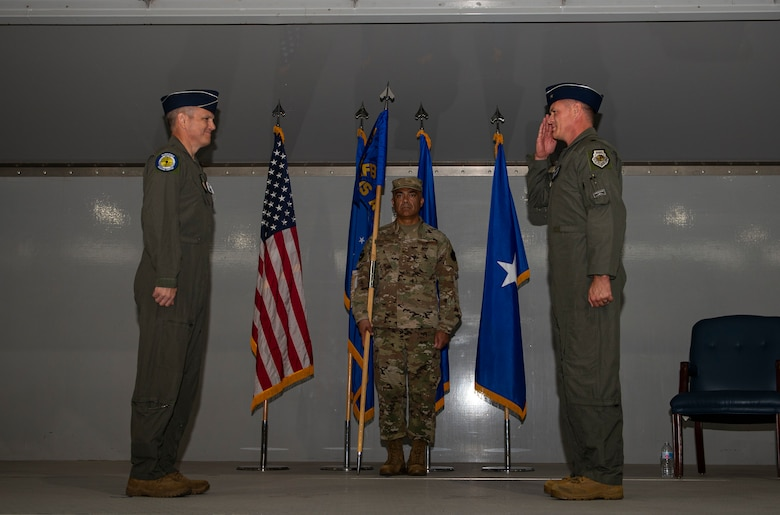 Brig. Gen. Michael Drowley salutes Maj. Gen. Charles Corcoran on stage during a ceremony.