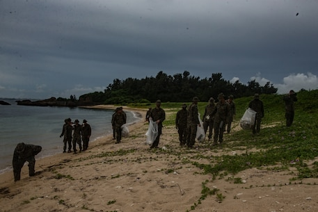 Marines with Combined Anti-Armor Team 1 (CAAT), Battalion Landing Team, 2nd Battalion, 4th Marines, 31st Marine Expeditionary Unit (MEU), clean the beach at Kin Blue, Okinawa, Japan, July 25, 2020. At the conclusion of their training, CAAT-1 picked up trash that had washed up on the beach in order to leave the environment better than they found it. The 31st MEU, the Marine Corps' only continuously forward-deployed MEU, provides a flexible and lethal force ready to perform a wide range of military operations as the premier crisis response force in the Indo-Pacific region. The 31st MEU has implemented strict health protection measures and will continue to conduct mission essential training in support of regional security and stability. (U.S. Marine Corps photo by Lance Cpl. Kolby Leger)