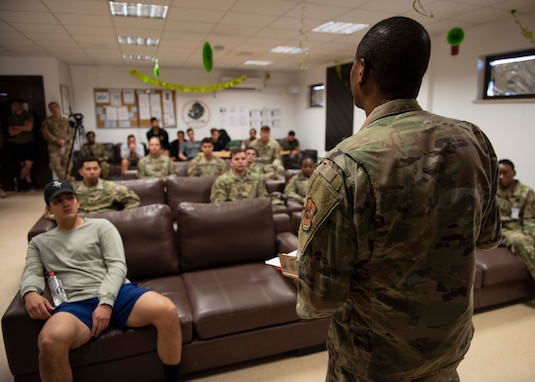 Soldiers sitting and listening to a speech given by another military member