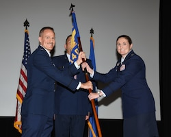 Col. Justin Spears, 14th Operations Group commander, hands Lt. Col. Jennifer Prouty, 14th Operations Support Squadron commander, the 14th OSS guidon at the 14th OSS change of command ceremony on Aug. 3, 2020, on Columbus Air Force Base, Miss. The 14th OSS is responsible for producing over 426 new pilots and WSOs annually. (U.S. Air Force photo by Sharon Ybarra)