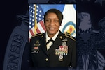 Black woman in Army dress uniform with ribbons and medals sits in front of US and Defense Commissary Agency flags.