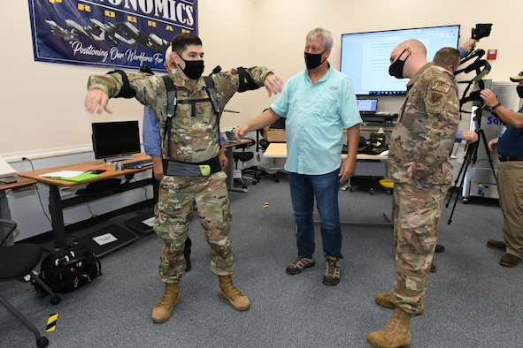 Photo shows three men with one putting on an upper body assist suit.