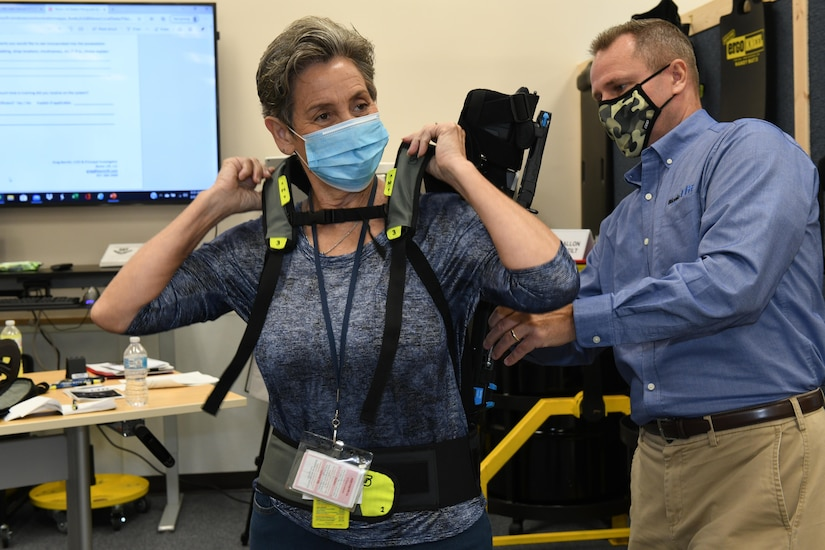 Photo shows a woman putting on an upper body exoskeleton suit.