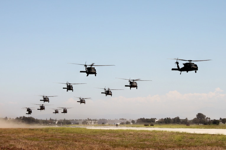 A large group of helicopters fly in formation close to the ground.