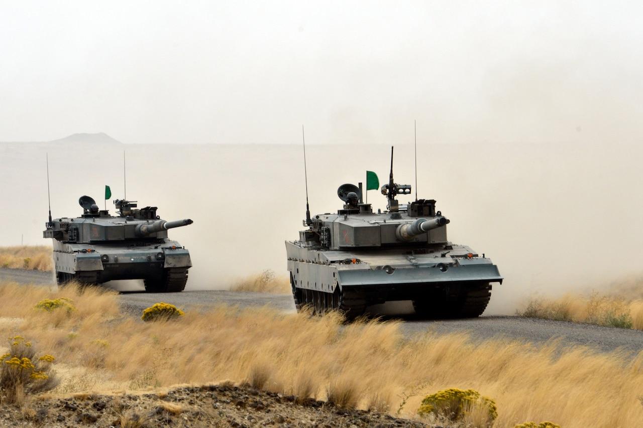 Tanks roll down a road.