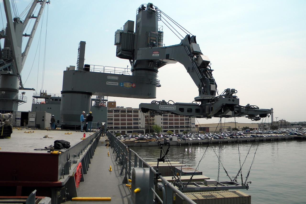 A crane, similar to a large robotic arm, moves toward a cargo container that is on a ship.