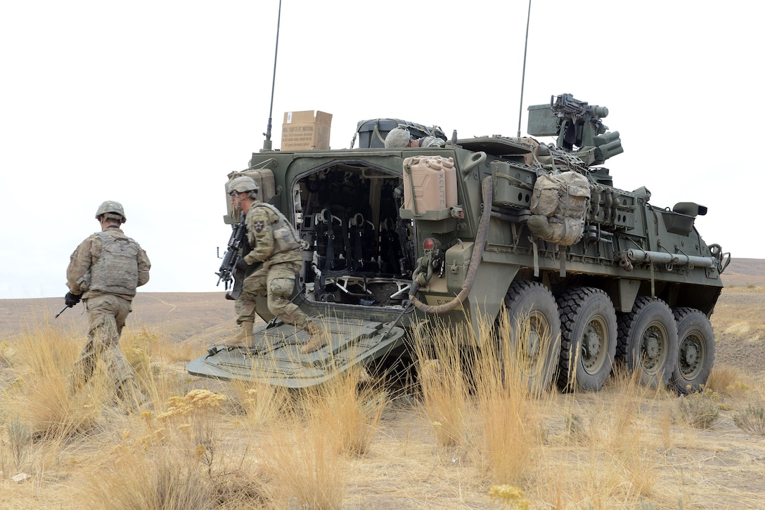 Military service members exit a combat vehicle.