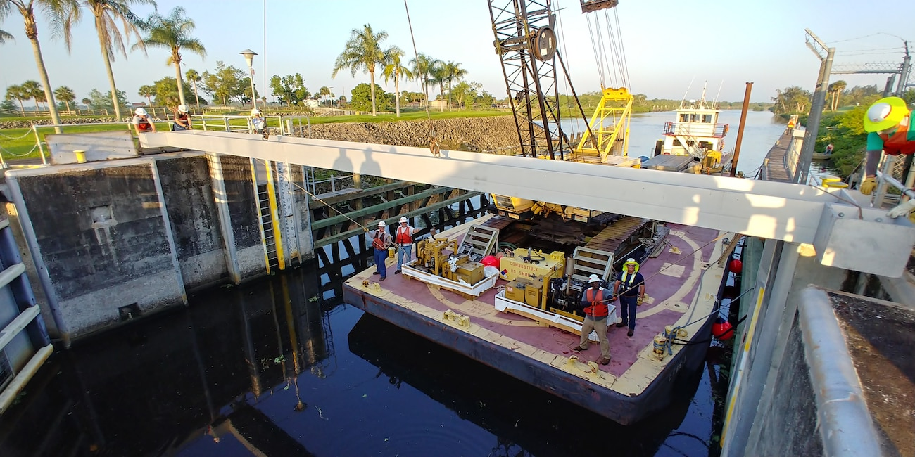 The crane operator and South Florida Operations team begin the dewatering of the Ortona Lock by setting a steel I-beam into the girder recess notch in the lock wall, starting with the upper end of the lock.