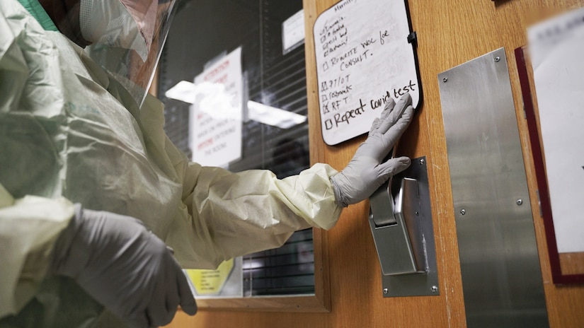 A nurse enters a COVID-19 patient room.