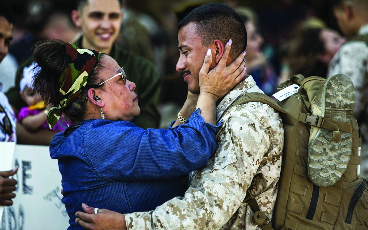 Solider and mother facing and looking at each other in welcome embrace with mother holding soldier's face in her hands.