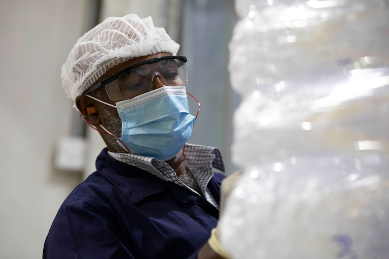 A government contractor wearing a face mask, protective eyewear and gloves marks a palate of packaged ice.