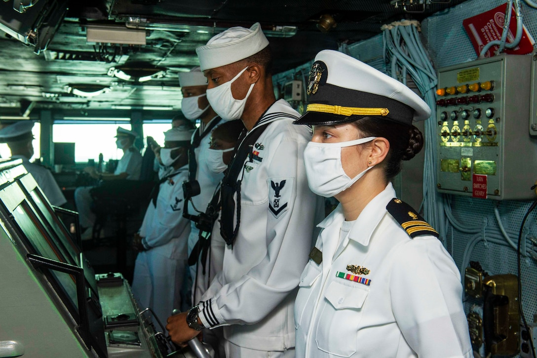 Sailors wearing face masks on the bridge of a ship.
