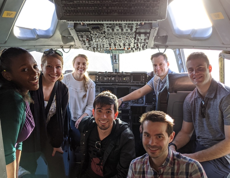 A team of civilians and Airmen researching artificial intelligence smiles in the cockpit of a C-17 Globemaster III.